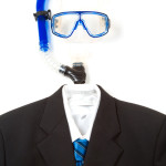 A shot of a business suit and tie with passport and snorkeling equipment